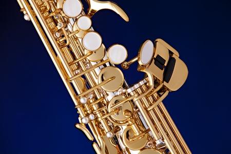 soprano saxophone: Un profesional de oro y plata, saxo soprano aislado contra un fondo negro.