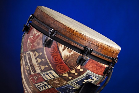 horizontal format horizontal: An African or Latin djembe drum isolated against a spotlight blue background in the horizontal format.