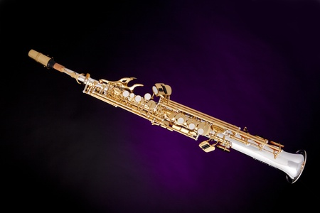 a professional soprano saxophone isolated against a spotlight purple background. photo
