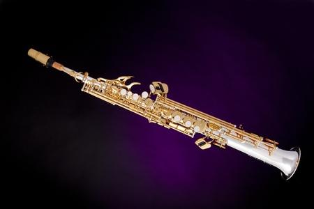 soprano saxophone: un saxofón soprano profesional aislado contra un fondo de spotlight púrpura.