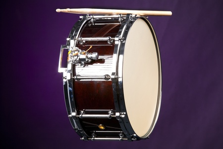 horizontal format horizontal: A wine colored snare drum isolated against a purple background in the horizontal format.
