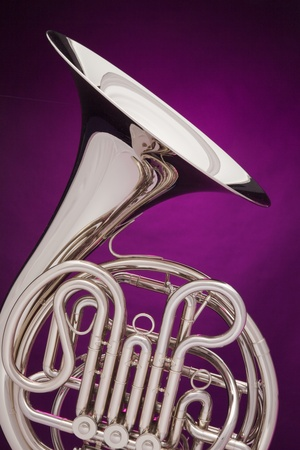 A professional double French horn isolated against a spotlight purple background. photo