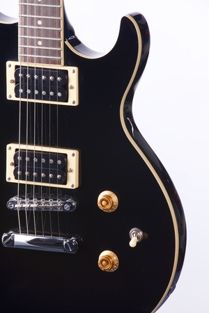 A black electric guitar isolated against a white background in the vertical format. photo