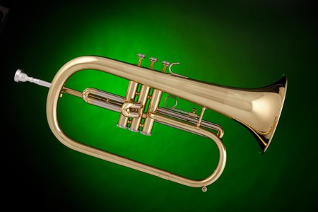 A gold flugalhorn trumpet isolated against a spotlight green background.