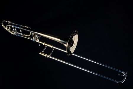 horizontal format horizontal: A complete trombone Isolated against a black background in the Horizontal format.