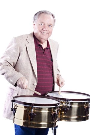 music background: A senior man with gray hair playing a set of gold color timbales against a white background.