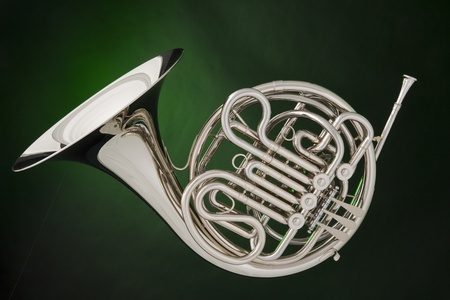 woodwind instrument: A professional double French horn isolated against a spotlight green background. Stock Photo