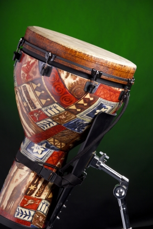 djembe drum: An African Latin djembe or conga drum isolated against a spotlight green background. Stock Photo
