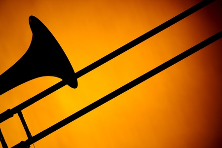 trombone: A trombone silhouette bell and slide Isolated against a spotlight gold background in the Horizontal format.