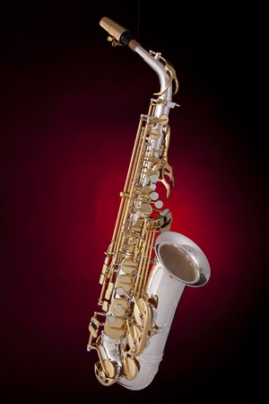 vertical format: A professional saxophone isolated against a red spotlight background in the vertical format. Stock Photo
