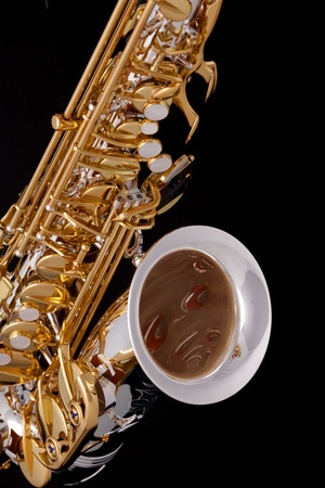vertical format: A professional saxophone isolated against a black background in the vertical format.
