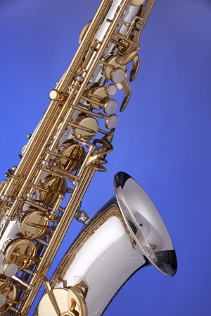 A professional gold and silver alto saxophone isolated against a blue background. photo