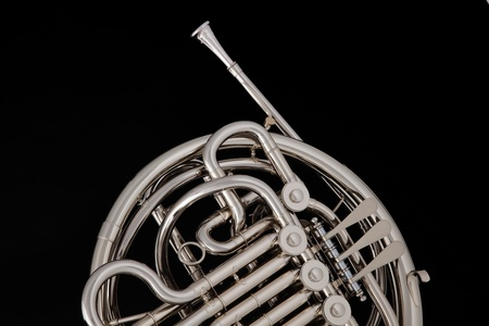 A silver professional French horn isolated against a black background with copy space.