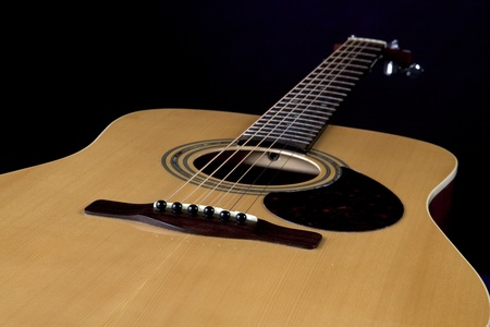 horizontal format horizontal: A wood acoustic guitar close up isolated on  a black background in the horizontal format.