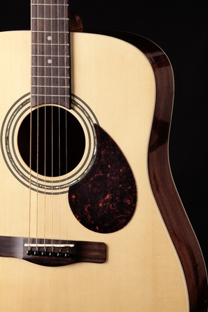 a natural wood  finish acoustic guitar isolated close  up on a black background. photo