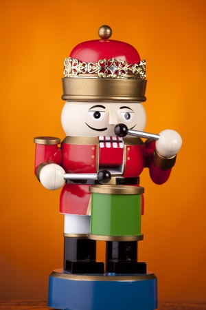 A Christmas toy marching soldier playing the drum isolated  on a gold background.