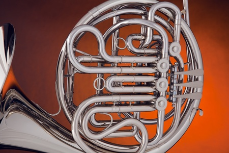 french horn: A professional silver French Horn isolated on a spotlight gold background.