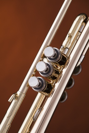 A gold brass trumpet music instrument against a spotlight gold background. photo