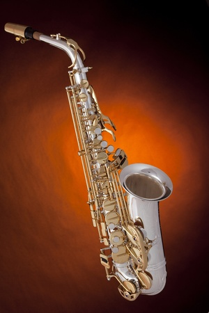 A professional silver and gold alto saxophone isolated against a spotlight dark yellow background. Stock Photo