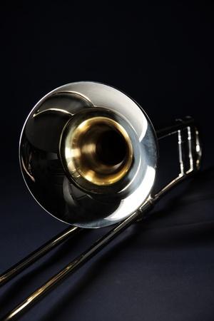 垂直方向の形式で黒い背景に対して隔離されるゴールドブラス トロンボーン。