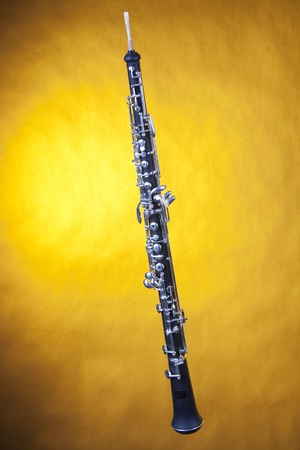 A wood oboe isolated against a spotlight yellow background in the vertical format.