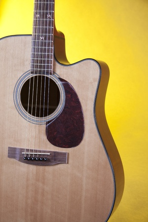 vertical format: An acoustic guitar isolated against a yellow background, in the vertical format.