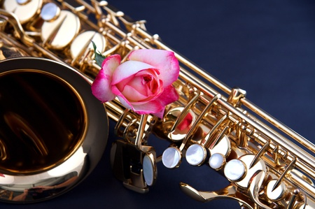 horizontal format horizontal: A gold brass saxophone with a pink rose isolated against a dark blue backgroundin the  horizontal format.
