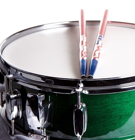 A green snare drum with sticks isolated against a white background in the square format. photo