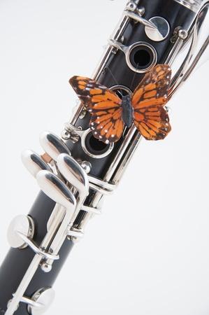 clarinete: Un clarinete soprano con una mariposa oro las claves aisladas sobre un fondo blanco en el formato vertical.