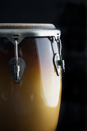 percussion: A brown Latin or African conga  drum isolated against a  black background in the vertical format with copy space. Stock Photo