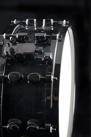 snare: A black chrome snare drum isolated on low key black background in the vertical  format with  copy space.