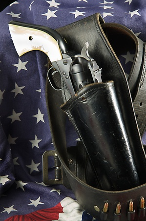 An old western six gun revolver isolated against  a flag background in the  vertical format,