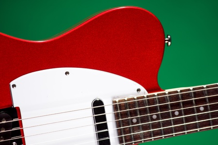 vertical format: An electric metallic red guitar isolated on a green background in the vertical format.