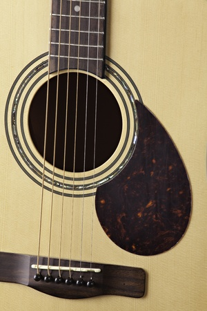 A natural finish acoustic guitar isolated close up and sharp. photo