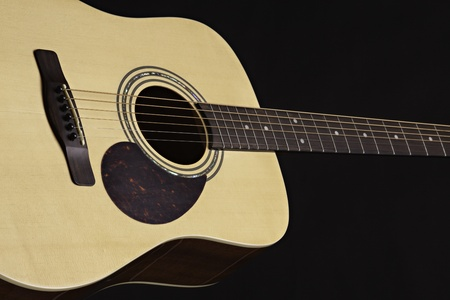 An natural finish acoustic guitar isolated against a black background. photo