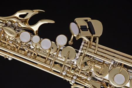 soprano saxophone: Un oro y plateado saxofón soprano aislado contra un fondo negro. Foto de archivo