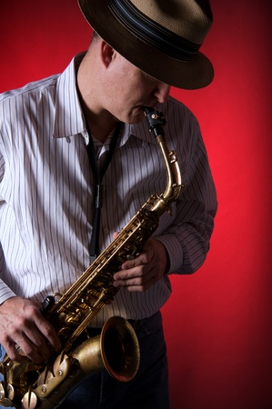 A professional saxophone player isolated against a red background in the vertical format with copy space. Stock Photo