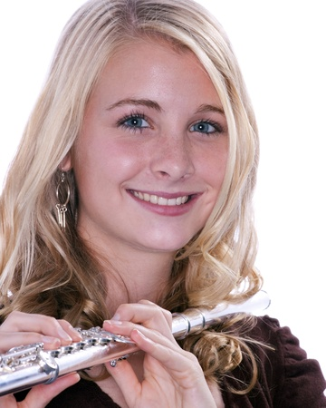 blue eyed: A blond blue eyed teenage female girl holding a silver flute against a white background.