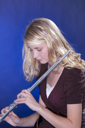 Een blonde tiener meisje met een zilveren dwarsfluit tegen een blauwe achtergrond. Stockfoto