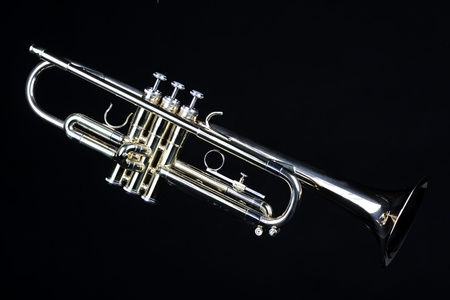 horizontal format horizontal: A gold brass trumpet isolated against a clean black background in the horizontal format.
