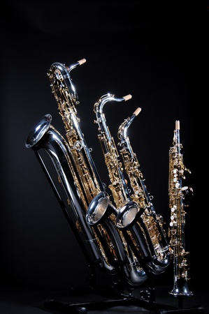 tenor: A set of four saxophones including a baritone, tenor, alto, and soprano isolated against a black background in the vertical format with copy space. Stock Photo