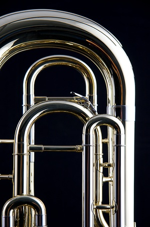tuba: A brass gold bass tuba euphonium isolated against a black background in the vertical format.