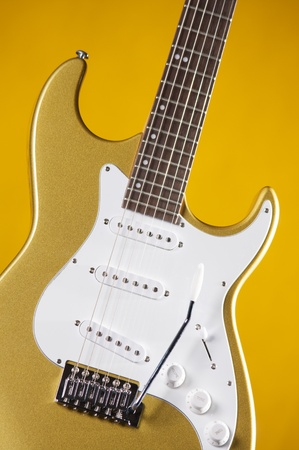 frets: A gold metallic electric guitar isolated against a yellow background in the vertical format.