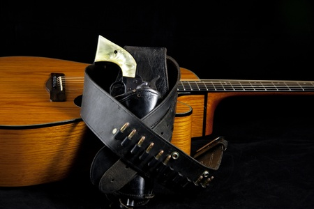 frets: A country western six gun in holster against a natural finish acoustic guitar in the vertical  format.