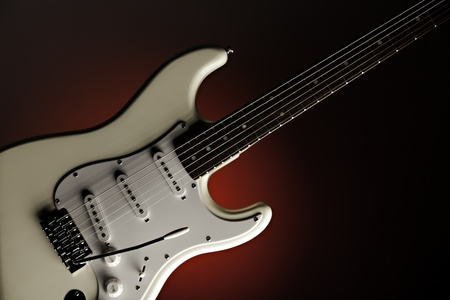 A white electric guitar isolated against a spotlight red background.