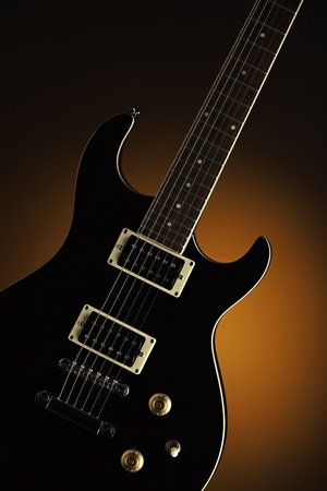 A black electric guitar isolated against a spotlight orange background