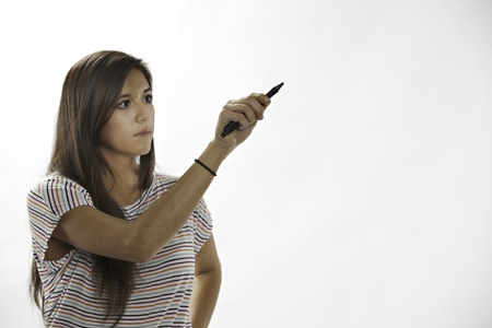 An attractive teenage female girl writing on a white background.