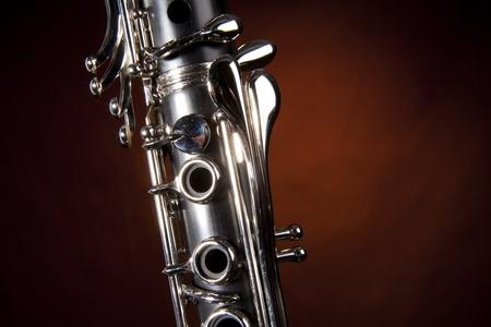 clarinete: Un clarinete soprano aislado contra un fondo reflector de oro en el formato horizontal.