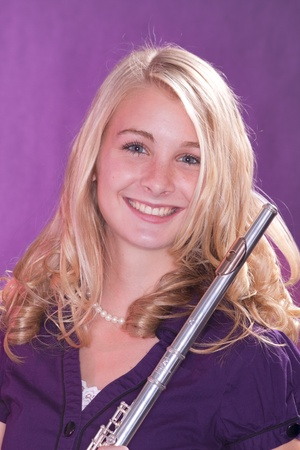 A blond blue eyed teenage female girl holding a silver flute against a pink background. photo