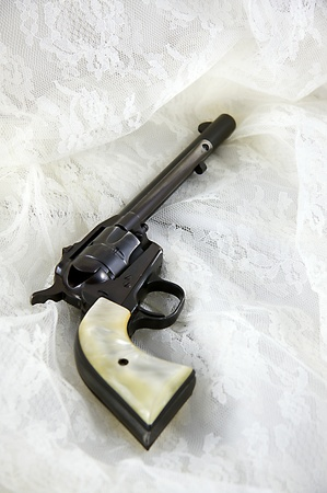 An old western six gun revolver isolated against  a white lace background in the  Vertical format with copy space.